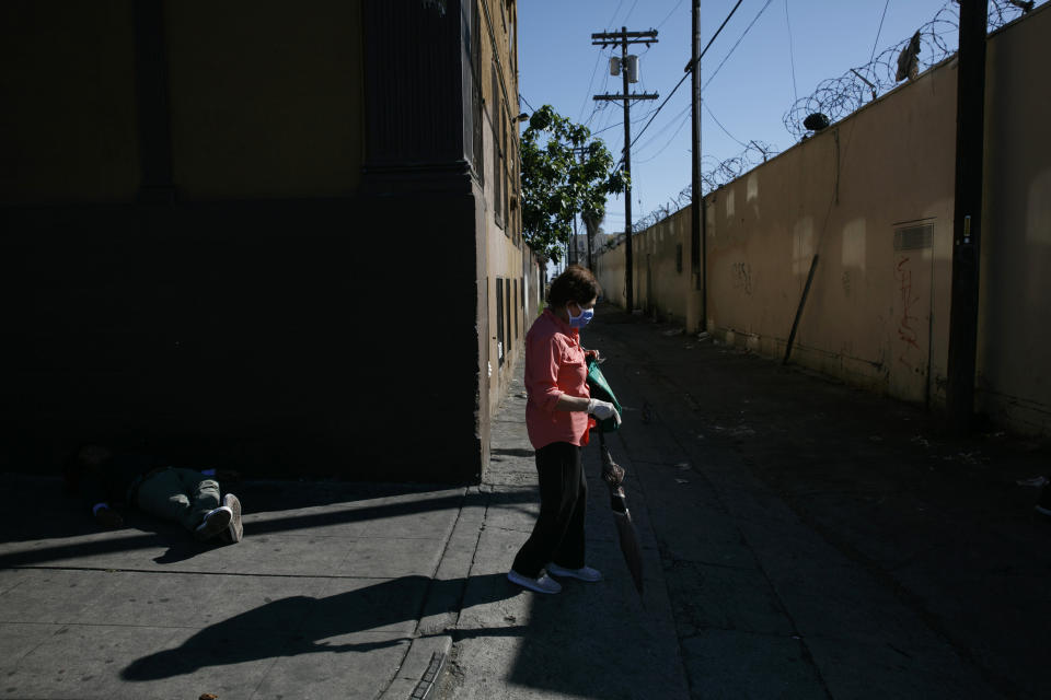 A woman with a mask and protective gloves walks past a homeless man napping on the street amid the coronavirus pandemic in the Westlake neighborhood of Los Angeles, Thursday, May 21, 2020. While most of California is welcoming a slight return toward normal this holiday weekend, Los Angeles will not be joining the party. The nation's largest county is not planning to reopen more widely until the next summer holiday, July 4th, because of a disproportionately large share of the state's coronavirus cases and deaths that have hampered the county's ability to rebound and meet strict criteria to get more people back to work.(AP Photo/Jae C. Hong)