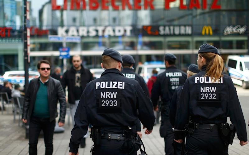 Police walks towards the Limbecker Platz shopping mall in Essen - Credit: Reuters