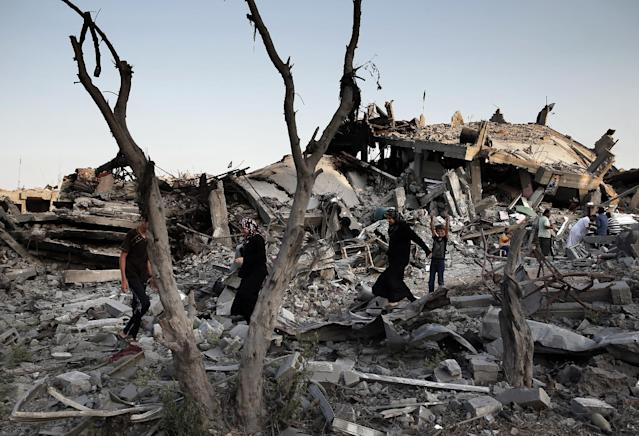 Palestinians walk in the rubble of destroyed houses in Gaza City's Shejaiya neighbourhood on August 17, 2014 (AFP Photo/Thomas Coex)