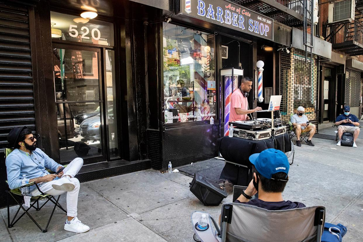 Customers wait on the sidewalk before receiving haircuts while a DJ plays outside Ace of Cuts barbershop, on Monday, June 22, 2020, in New York.