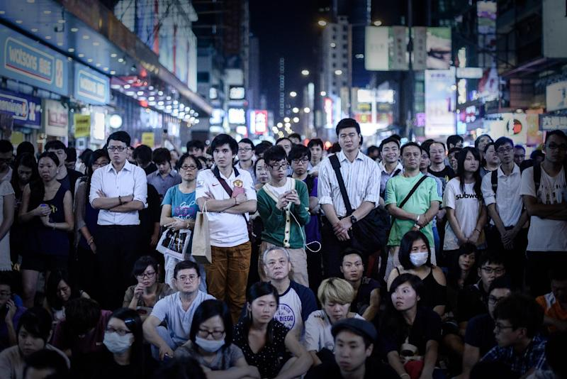 People listen to long-awaited talks between student leaders and senior government officials being broadcast live at a protest site in the Mongkok district of Hong Kong on October 21, 2014 (AFP Photo/Philippe Lopez)