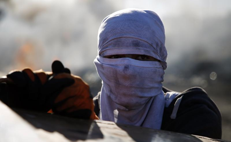 A masked Palestinian protestor takes cover behind a bin during clashes with Israeli forces near an Israeli checkpoint in the West Bank city of Ramallah on December 16, 2017 (AFP Photo/ABBAS MOMANI)