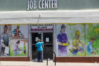 FILE - In this May 7, 2020, file photo, a person looks inside the closed doors of the Pasadena Community Job Center during the coronavirus pandemic in Pasadena, Calif. California added more than 140,000 jobs in July and lowered its unemployment rate to 13.3%. But the unemployment rate is still higher than it ever was during the Great Recession a decade ago. (AP Photo/Damian Dovarganes, File)