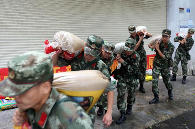 <p>Frontier soldiers carry sand bags after typhoon Hato landed on Aug. 23, 2017 in Shenzhen, Guangzhou Province of China. (Photo: VCG via Getty Images) </p>