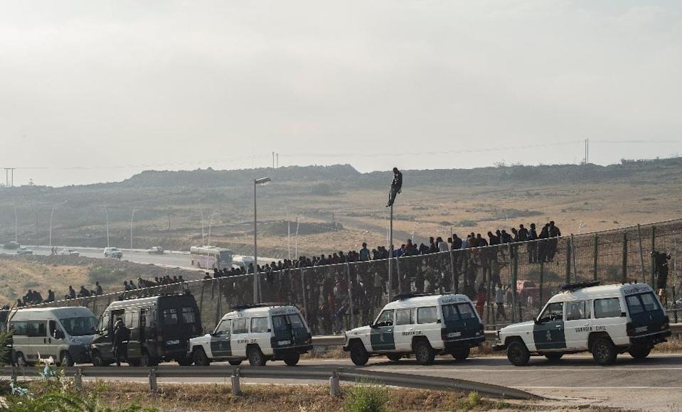 Members of the Guardia Civil stand next to their vehicles as would-be immigrants sit atop a boarder fence separating Morocco from the north African Spanish enclave of Melilla on May 1, 2014 (AFP Photo/Blasco de Avellaneda)