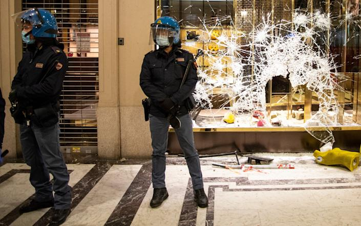 Police officers stand guard outside a Gucci boutique store as protesters gather during an anti government demonstration in Turin - Getty