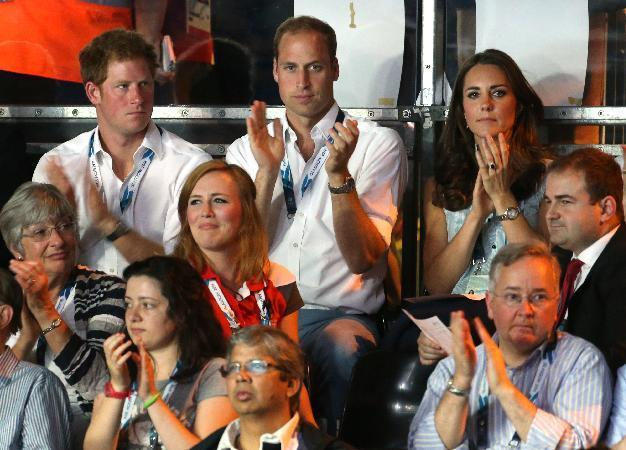 Britain's Prince William,top centre, sits next to his wife Kate, Duchess of Cambridge and Prince Harry applaud as they watch boxing bouts at the Commonwealth Games Glasgow 2014, in Glasgow, Scotland, Monday, July, 28, 2014. (AP Photo/Peter Morrison)