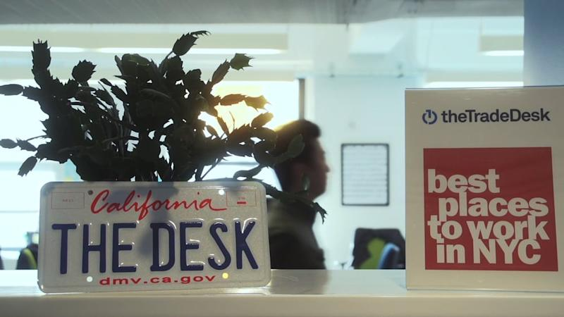 The Trade Desk reception area at its headquarters featuring a potted plant behind a license plate with The Desk California etched on it.