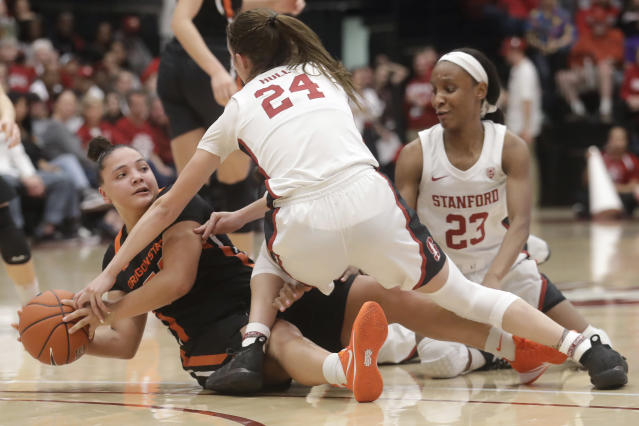 Oregon State guard Destiny Slocum, bottom left, tries to pass the ball while being defended by Stanford guard Lacie Hull, middle, and guard Kiana Williams (23) during the second half of an NCAA college basketball game in Stanford, Calif., Friday, Feb. 21, 2020. (AP Photo/Jeff Chiu)