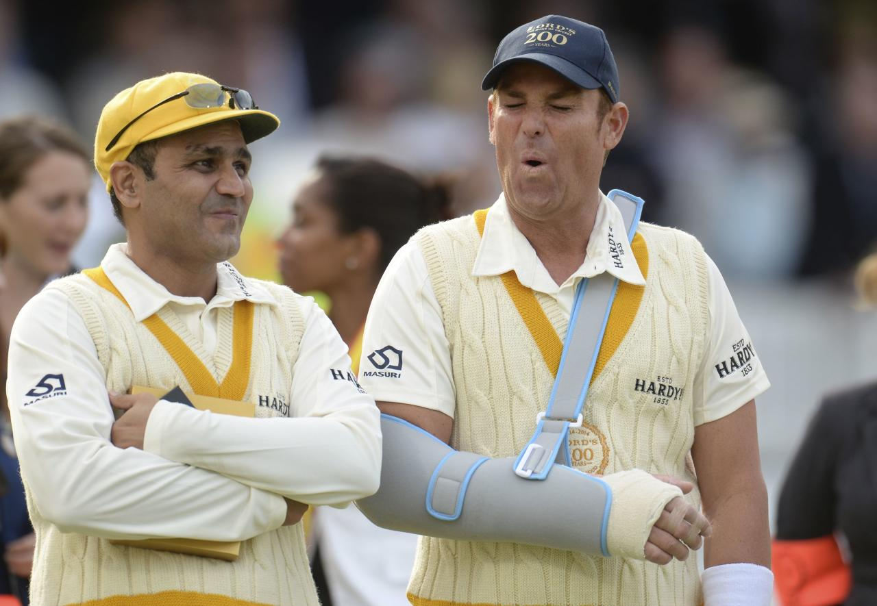 Rest of the World's captain Shane Warne waits for the presentations with teammate Virender Sehwag (L) after the cricket match against MCC to celebrate 200 years of Lord's at Lord's cricket ground in London, July 5, 2014. REUTERS/Philip Brown (BRITAIN - Tags: SPORT CRICKET)