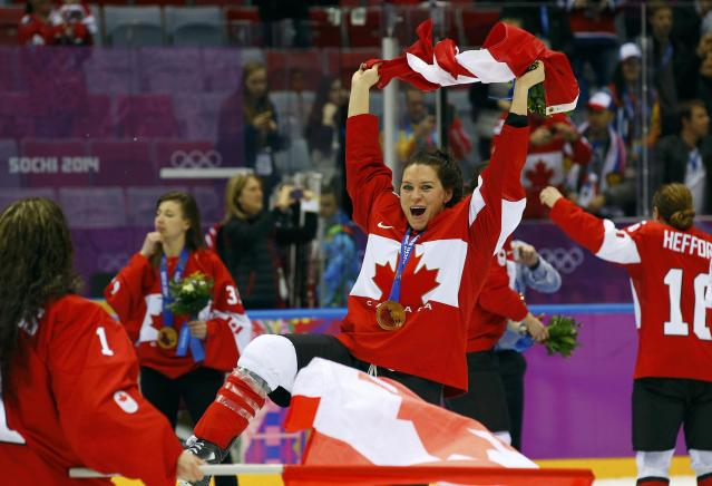Canada's Natalie Spooner waves the Canadian flag as she celebrates with teammates after winning their gold medal ice hockey game against Team USA at the 2014 Sochi Winter Olympic Games February 20, 2014. REUTERS/Brian Snyder (RUSSIA - Tags: OLYMPICS SPORT ICE HOCKEY)