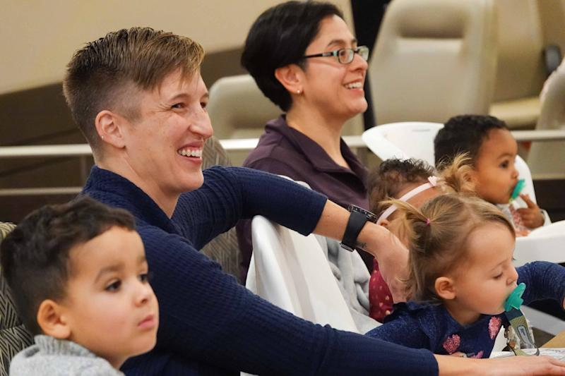 Dr. Erin Meyer and her wife and Dr. Sandra Medinilla sit with their four adopted children during an adoption ceremony for their fourth child, 6-month-old Sydney.