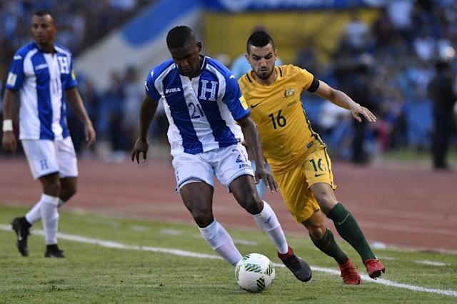 Honduras' Brayan Beckeles (C) drives the ball past Australia's Aziz Behich during their FIFA 2018 World Cup qualifying play-off first leg match, in San Pedro Sula, Honduras, on November 10, 2017 (AFP Photo/Johan ORDONEZ)