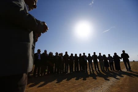 Turkish Kurds and clerics pray near the Mursitpinar border crossing, on the Turkish-Syrian border in the southeastern town of Suruc in Sanliurfa province October 25, 2014. REUTERS/Kai Pfaffenbach