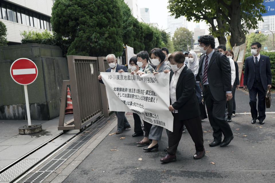 """Plaintiffs and their supporters arrive at the Tokyo District Court Thursday, Oct. 14, 2021, in Tokyo. The court is hearing five ethnic Korean residents of Japan and a Japanese national demanding the North Korean government pay compensation over their human rights abuses in that country after joining a resettlement program there that promised a """"paradise on Earth,"""" but without the presence of a defendant - the North's leader. The banner on top reads: """"Oct. 14 Tokyo District Court the North Korea """"Paradise on Earth"""" campaign first trial. (AP Photo/Eugene Hoshiko)"""