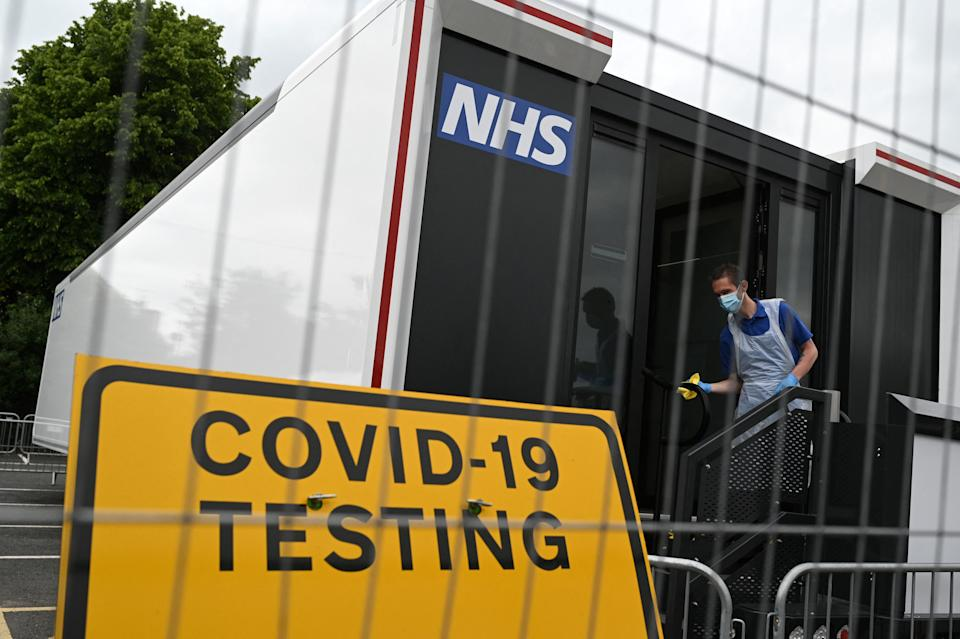 A worker cleans down the doorway of a Covid-19 testing centre set up a car park in Penrith in Cumbria, north west England on June 21, 2021, following an outbreak of a coronavirus variant of concern. (Photo by Oli SCARFF / AFP) (Photo by OLI SCARFF/AFP via Getty Images)