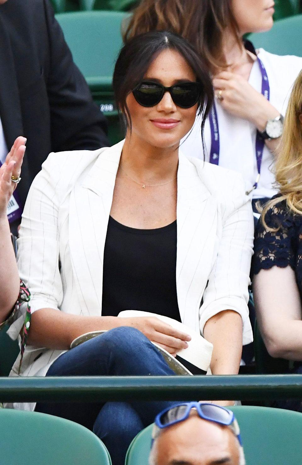 """<p>While at Wimbledon to support friend Serena Williams, Meghan kept Archie close <a href=""""https://people.com/royals/all-about-meghan-markles-meaningful-gold-necklace-to-honor-son-archie/"""" rel=""""nofollow noopener"""" target=""""_blank"""" data-ylk=""""slk:with a delicate Verse necklace featuring his initial"""" class=""""link rapid-noclick-resp"""">with a delicate Verse necklace featuring his initial</a>. </p>"""