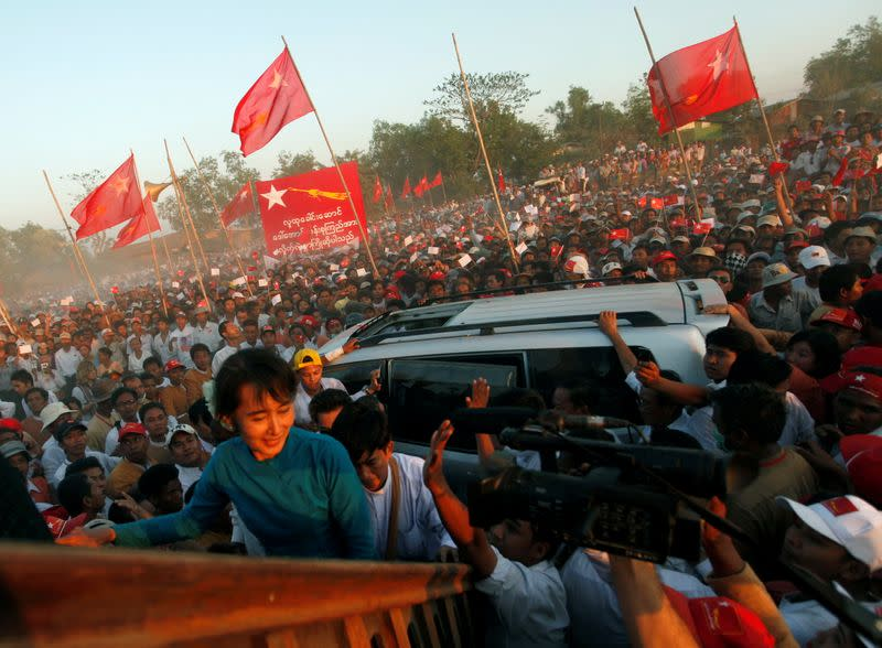 FILE PHOTO: Supporters wave their hands as Myanmar pro-democracy leader Aung San Suu Kyi arrives at Thone Khwa township