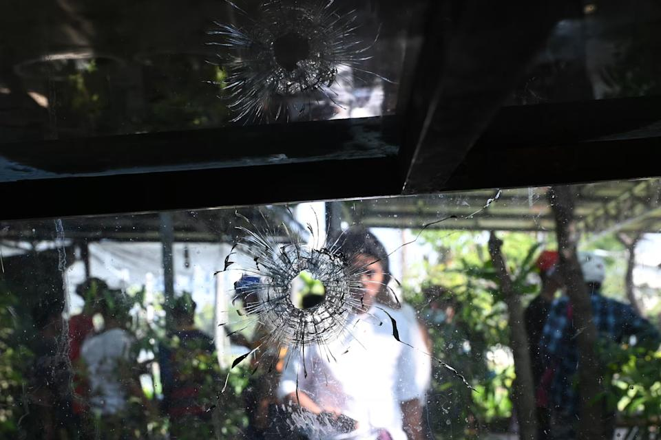 A woman looks at a bullet hole on a glass cover of a food stall in Yangon on March 4, 2021, a day after where protesters were shot and died by gun fire as security forces dispersed a demonstration against the military coup. (Photo by STR / AFP) (Photo by STR/AFP via Getty Images)