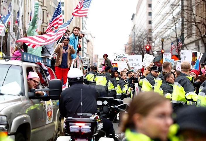 Police block demonstrators who surrounded a parade float with Donald Trump supporters during the Women's March in Washington, DC (AFP Photo/Joshua LOTT)