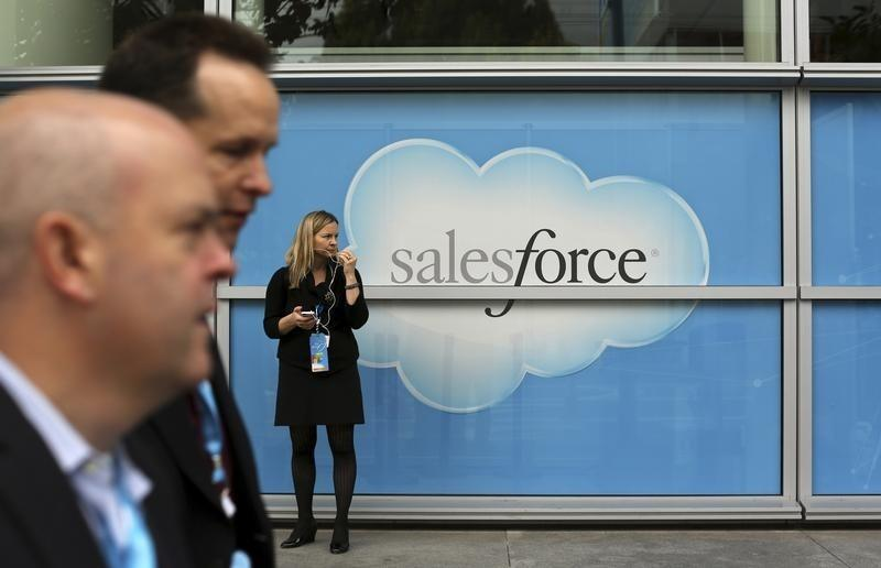 Woman stands near a Salesforce sign during the company's annual Dreamforce event, in San Francisco
