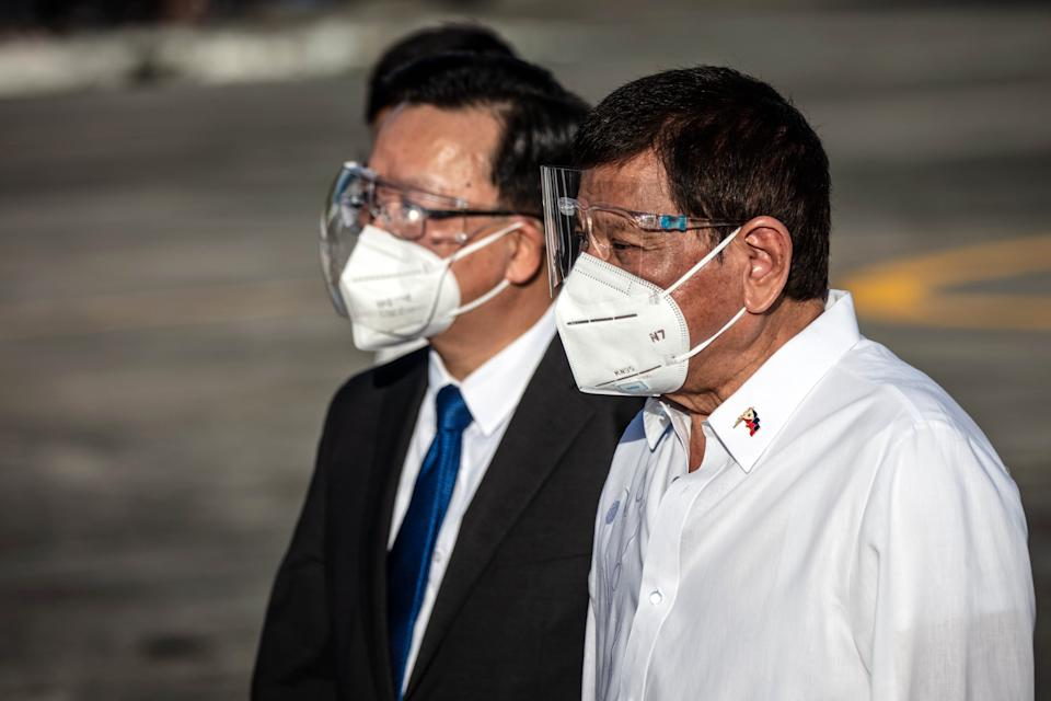 FILE PHOTO: China's Ambassador to the Philippines Huang Xilian (L) and President Rodrigo Duterte watch as crates containing Sinovac Biotech COVID-19 vaccines arrive on a Chinese Airforce plane at Ninoy Aquino International Airport on February 28, 2021 in Manila, Philippines. (Photo: Ezra Acayan/Getty Images)