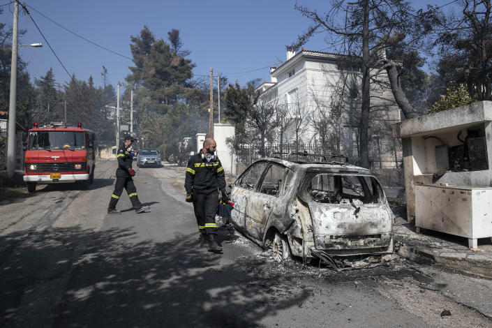 Firefighters look at a burnt car following a forest fire at Dionysos northern suburb of Athens, on Tuesday, July 27, 2021. Greek authorities have evacuated several areas north of Athens as a wildfire swept through a hillside forest and threatened homes despite a large operation mounted by firefighters. (AP Photo/Yorgos Karahalis)