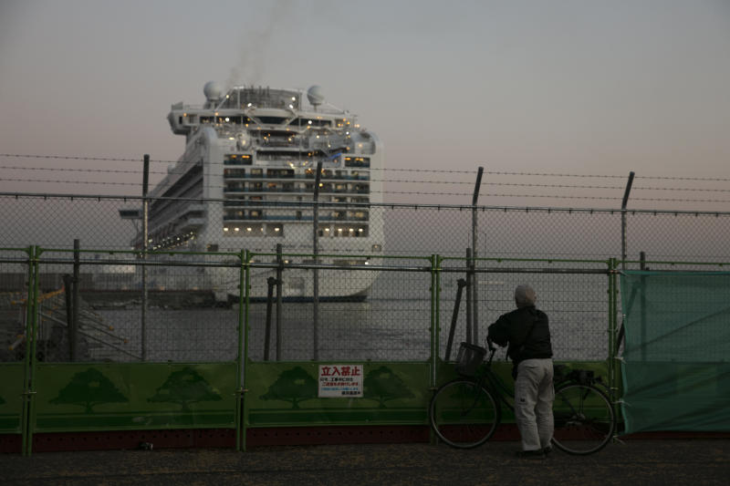 A man looks at the the quarantined Diamond Princess cruise ship Thursday, Feb. 13, 2020, in Yokohama, near Tokyo. Life on board the luxury cruise ship, which has dozens of cases of a new virus, can include fear, excitement and soul-crushing boredom, according to interviews by The Associated Press with passengers and a stream of tweets and YouTube videos. (AP Photo/Jae C. Hong)