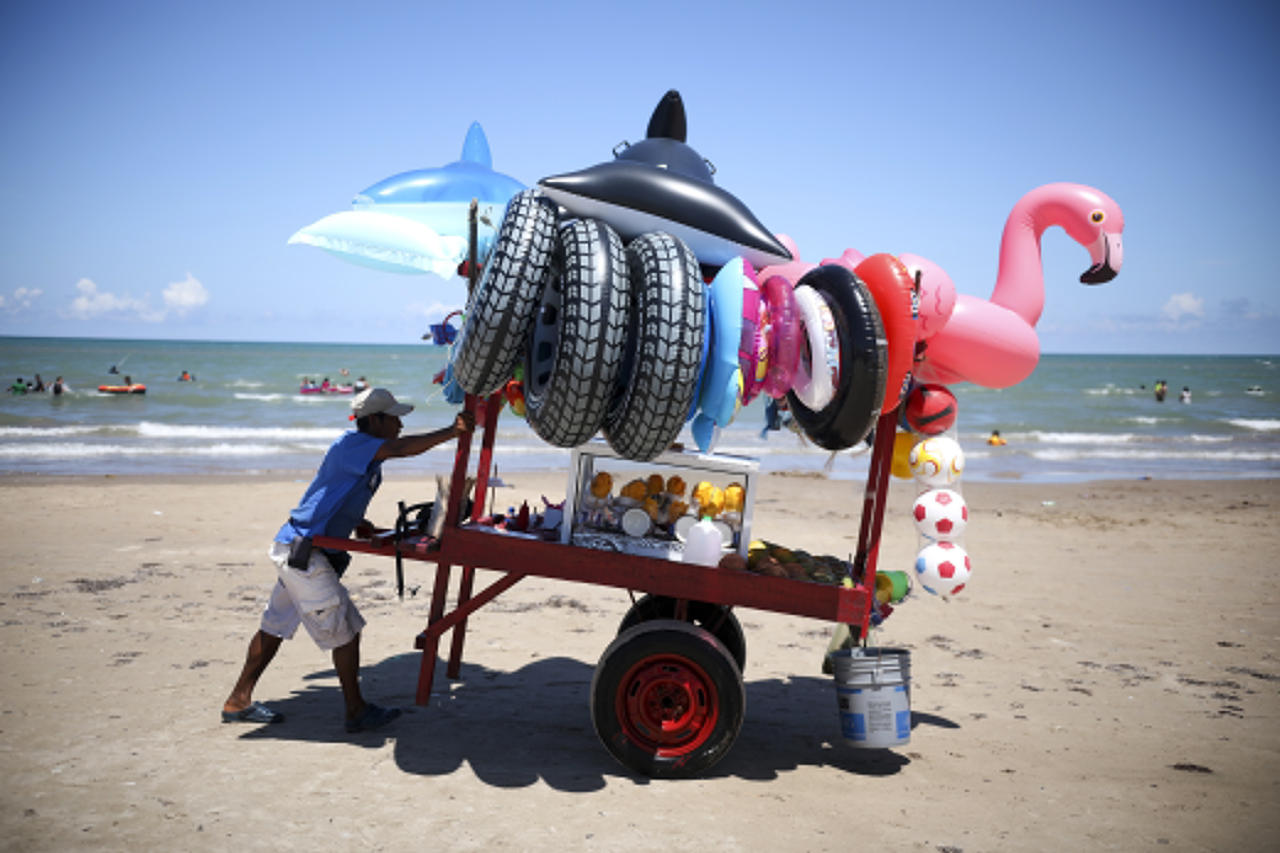 In this Aug. 3, 2019 photo, a vendor pushes his cart equipped with inflatable pool toys and fruit cups along the shoreline of Playa Bagdad near the border city of Matamoros, Mexico. Locals view it as a place where it is best to keep out of trouble. (AP Photo/Emilio Espejel)