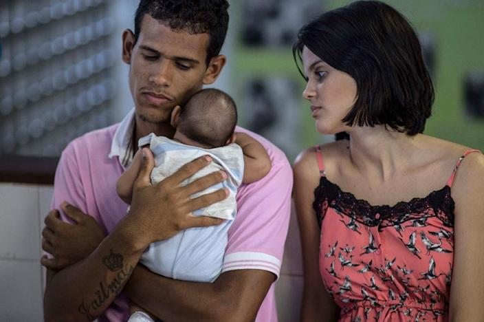 Parents tend their two-month-old son suffering from microcephaly, in Salvador, Brazil on January 27, 2016 (AFP Photo/Christophe Simon)