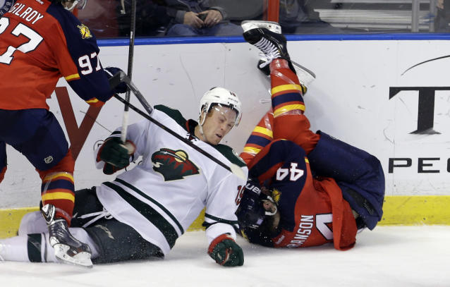 Minnesota Wild center Stephane Veilleux (19) falls after checking Florida Panthers defenseman Erik Gudbranson (44) in the second period of an NHL hockey game, Saturday, Oct. 19, 2013, in Sunrise, Fla. (AP Photo/Alan Diaz)