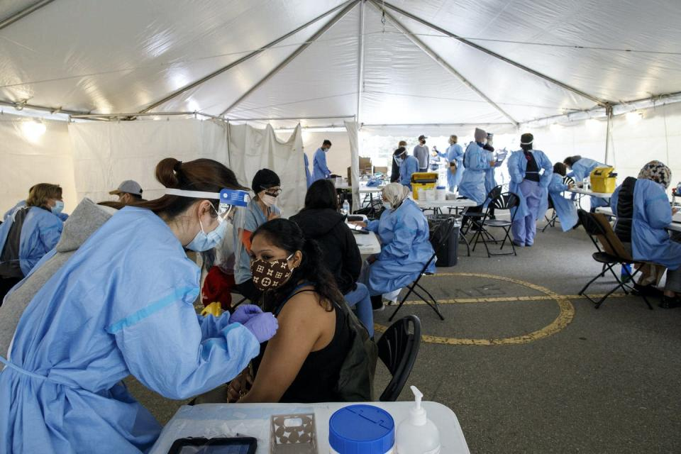 People in masks are vaccinated by health-care workers in protective gear inside a tent