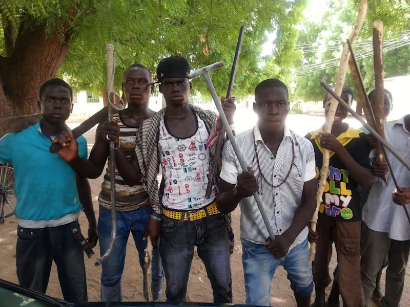"In this photo taken with a mobile phone Tuesday, June 11, 2013, Vigilantes youths pose for a photographs in Maiduguri, Nigeria. As soldiers continue an offensive against radical Islamic extremists in northeast Nigeria, young men armed with machetes and sticks have now entered the streets of the region's biggest city, targeting suspected fighters. The members of the ""Civilian JTF,"" a play off the acronym used to describe the joint military and police taskforce in the region, already have come under attack from extremists for pointing out suspects to soldiers. However, it remains unclear what happens to those the group points out, as some suspects in Maiduguri have already been shot dead by security forces and left rotting in ditches in the city.(AP Photo/Abdulkareem Haruna)"