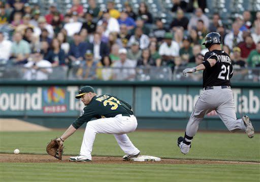 Oakland Athletics first baseman Brandon Moss, left, digs up a low throw from shortstop Jed Lowrie to put out Chicago White Sox's Tyler Flowers (21) during the third inning of a baseball game on Friday, May 31, 2013, in Oakland, Calif. (AP Photo/Marcio Jose Sanchez)