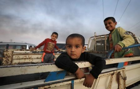 FILE PHOTO: Boys stand at a back of a truck as they flee Ras al Ain town