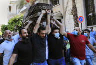 Mourners carry the coffin of Ibrahim Harb, 35, who was critically injured in the massive explosion at Beirut's port last year and who died on Monday nearly 14 months after the blast, in Beirut, Lebanon, Tuesday, Sept. 28, 2021. On Aug. 4, 2020, hundreds of tons of ammonium nitrate, a highly explosive material used in fertilizers, ignited after a massive fire at the port. The death brings to at least 215 the number of people who have been killed by the blast, according to official records. (AP Photo/Hussein Malla)