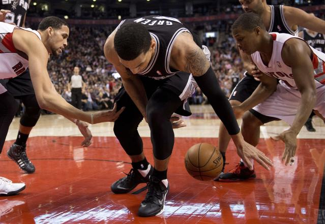 San Antonio Spurs guard Danny Green, center, loses control of the ball to Toronto Raptors guard Kyle Lowry, right, and forward Austin Daye during the first half of an NBA basketball game in Toronto on Tuesday, Dec. 10, 2013. (AP Photo/The Canadian Press, Frank Gunn)