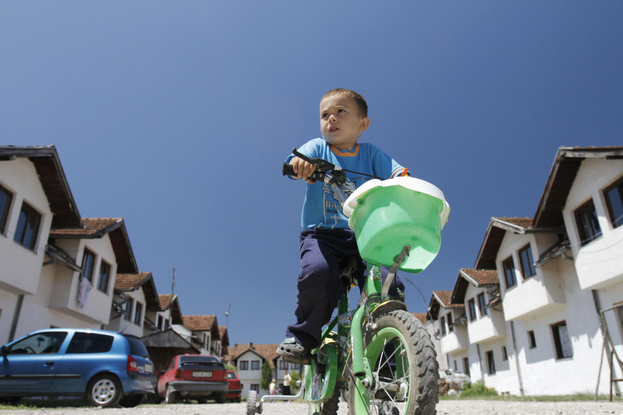 Bosnian Muslim Mujo Golic, 4, celebrates his birthday as he rides through the collective center for refugees near the northern Bosnian town of Zivinice, 130 kms north of Sarajevo, Monday, June 20, 2011, where his family settled after being displaced from their home in eastern Bosnia in 1995. Many refugees and internal displaced persons war still live in primitive shelters waiting to return to their destroyed pre-war homes, 16 years after the 1992-95 Bosnian war. On World Refugee Day, which is marked in Bosnia today, a total of 43.7 million displaced people have been registered in the world, 15.4 million of whom are refugees.(AP Photo/Amel Emric)