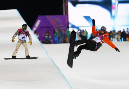 Shaun White of the United States waits on the edge of the half pipe during a snowboard half pipe training session at the Rosa Khutor Extreme Park at the 2014 Winter Olympics, Monday, Feb. 10, 2014, in Krasnaya Polyana, Russia. (AP Photo/Sergei Grits)
