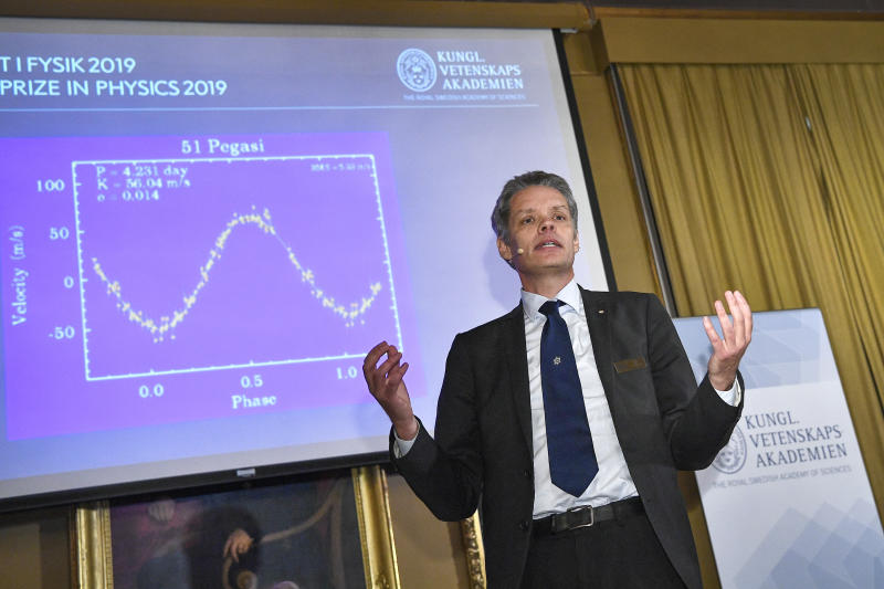 Ulf Danielsson, member of the Nobel committee talks during the announcement of the winners of the 2019 Nobel Prize in Physics during news conference at the Royal Swedish Academy of Sciences in Stockholm, Sweden, on Tuesday Oct. 8, 2019.  The 2019 Nobel Prize in Physics is awarded to James Peebles, Michel Mayor and Didier Queloz. (Claudio Bresciani / TT via AP)