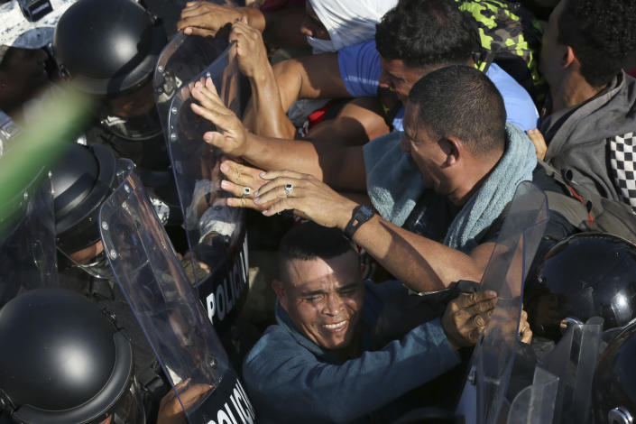 Migrants scuffle with Mexican National Guardsmen at the border crossing between Guatemala and Mexico in Tecun Uman, Guatemala, Saturday, Jan. 18, 2020. More than a thousand Central American migrants surged onto a bridge spanning the Suchiate River that marks the border between both countries as Mexican security forces attempted to impede their journey north. (AP Photo/Marco Ugarte)