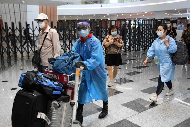 PHOTO: Travelers wear face masks amid concerns of the novel coronavirus as they arrive from a flight at Beijing Daxing International Airport on the eve of a five-day national holiday in China on April 30, 2020. (Greg Baker/AFP via Getty Images)