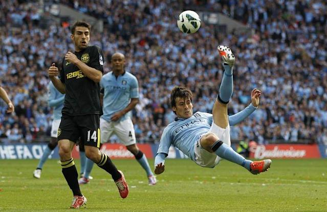 Manchester City's midfielder David Silva (R) attempts an overhead kick in the penalty area as Wigan Athletic's midfielder Jordi Gomez (L) looks on during their English FA Cup final football match at Wembley Stadium in London on May 11, 2013. Wigan won 1-0