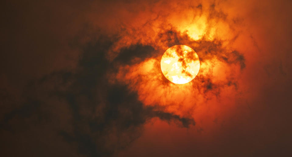 Sun through dark smoke clouds from bushfires with red glow, during climate change in Australia. Source: Getty Images