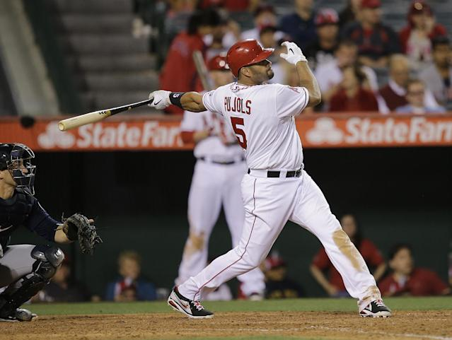 Los Angeles Angels' Albert Pujols watches the flight of his home run during the eighth inning of a baseball game against the Seattle Mariners in Anaheim, Calif., Tuesday, June 18, 2013. (AP Photo/Jae C. Hong)