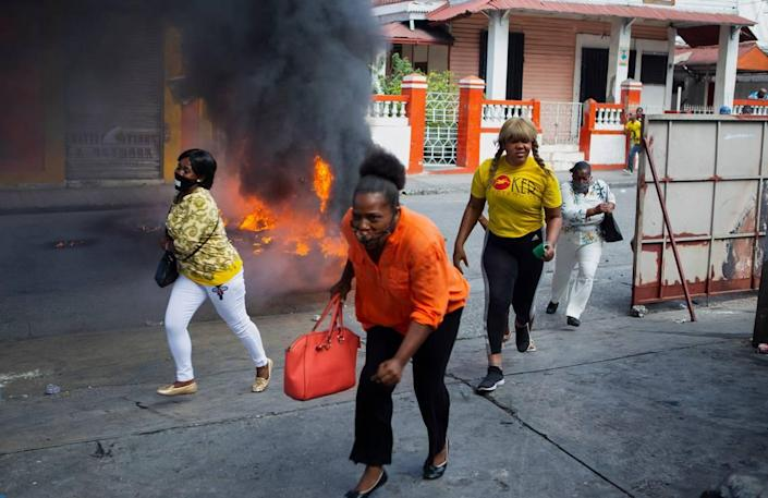People run past a burning barricade during a demonstration demanding the resignation of President Jovenel Moïse, in Port-au-Prince, Haiti, Friday, Jan. 15, 2021.