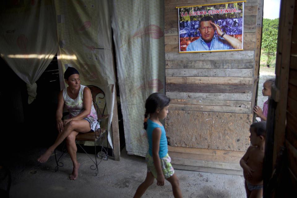 """In this April 8, 2013 photo, Yadaira Nunez, 43, sits in her wooden shack next to a poster of Venezuela's late President Hugo Chavez that reads in Spanish; """"The battle continues...,"""" at a squatter settlement near Tacarigua, Venezuela. Outside Venezuela's capital, power outages, food shortages and unfinished projects abound; important factors heading into Sunday's election to replace Chavez, who died last month after a long battle with cancer. An estimated 2 million of Venezuela's country's nearly 30 million people lack permanent homes, and one of Chavez's anti-poverty """"missions"""" builds them. But it's been slow going. The government says it has built 370,500 homes and apartments over the past two years, and more than 3 million people applied for them. (AP Photo/Ramon Espinosa)"""