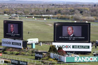 Video screens show pictures of the late Prince Philip, Duke of Edinburgh, ahead of the races on the second day of the Grand National Horse Racing meeting at Aintree racecourse, near Liverpool, England, Friday April 9, 2021. Buckingham Palace says Prince Philip, the irascible and tough-minded husband of Queen Elizabeth II, has died. He was 99. (AP Photo/Scott Heppell, Pool)