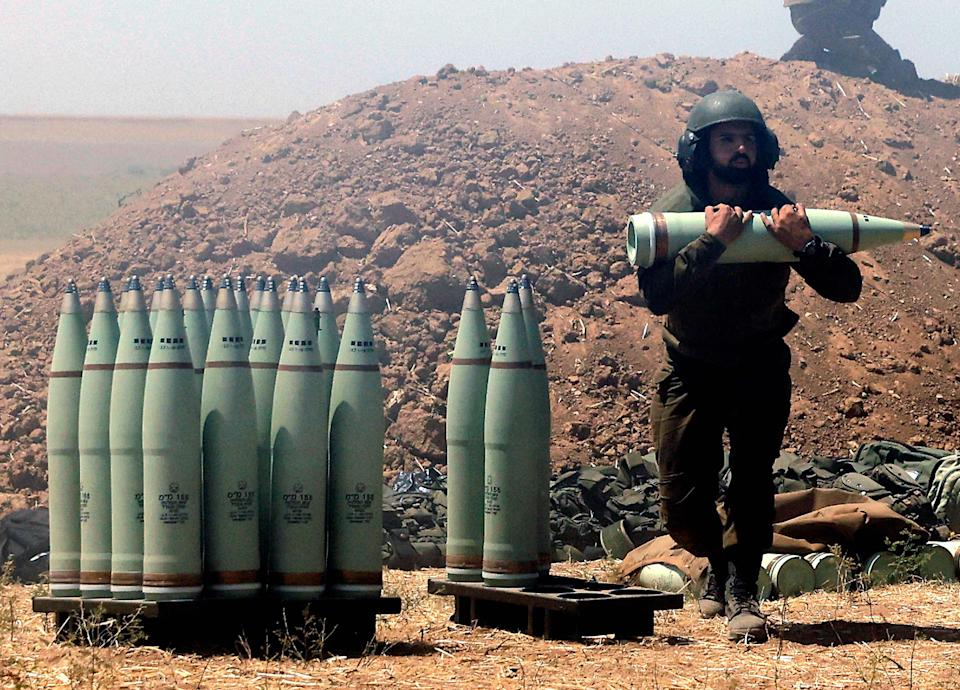 <p>An Israeli soldiers carries artillery shells due to be fired towards the Gaza Strip</p> (AFP via Getty Images)