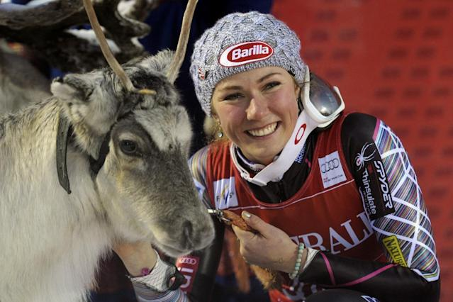 Mikaela Shiffrin of the US, reacts with a reindeer, part of her prize for winning the women's FIS Alpine Ski World Cup, in Levi, Finnish Lapland , Saturday, Nov. 16, 2013. (AP Photo /Lehtikuva, Markku Ulander) FINLAND OUT